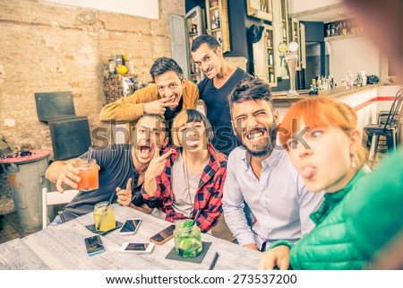 Group of friends having fun in a cocktail bar and taking a selfie - Young students partying together and taking picture - Concepts about fun,youth,technologies and nightlife - stock photo