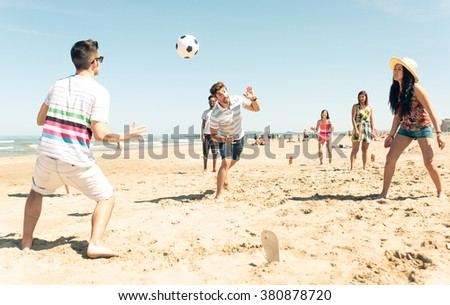 Group of friends having fun on the beach playing soccer. happy people and beach games concept - stock photo