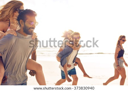 Group of friends having fun on the beach, Young men piggybacking women on the sea shore. Mixed race young people enjoying summer vacation. - stock photo