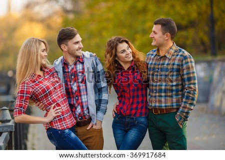 Group Of Friends Having Fun Together Outdoors. Happy group of friends talking and having fun outdoors. four friends of women and men smiling and walking along summer park - stock photo