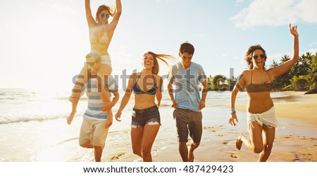 Group of friends having fun walking down the beach at sunset