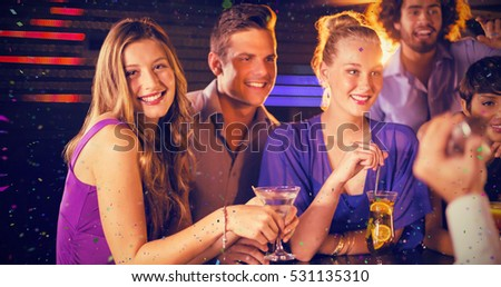 Group of friends having glass of cocktail at bar counter against flying colours