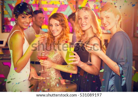 Group of friends having glass of cocktail in bar against flying colours