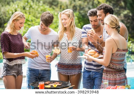 Group of friends having hamburgers and juice at outdoors barbecue party - stock photo