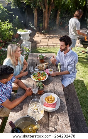 group of friends having outdoor garden barbecue dinner party - stock photo