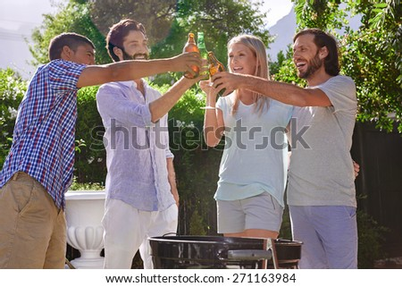 group of friends having outdoor garden barbecue laughing toasting with alcoholic beer drinks - stock photo