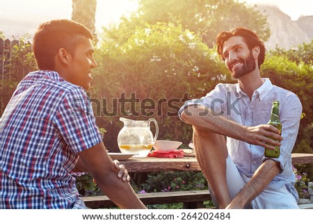 group of friends having outdoor garden dinner party with beer drinks - stock photo