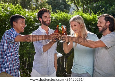group of friends having outdoor garden party toast with alcoholic beer drinks - stock photo