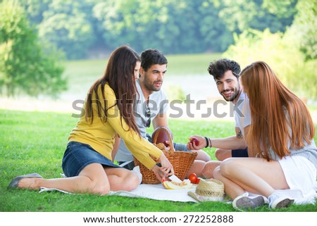 Group of friends having picnic on green meadow - stock photo