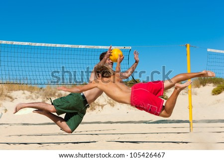 Group of friends � here two men to be seen - playing beach volleyball, they are jumping after the ball
