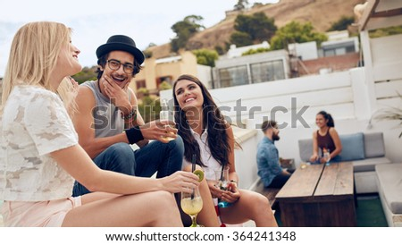Group of friends holding drink and chatting on the roof. Young people hanging out on rooftop and  having party. - stock photo
