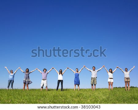 Group of friends holding hands in meadow under blue sky - stock photo