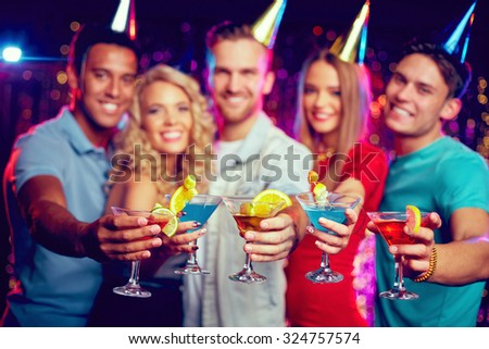 Group of friends holding martini glasses with cocktails