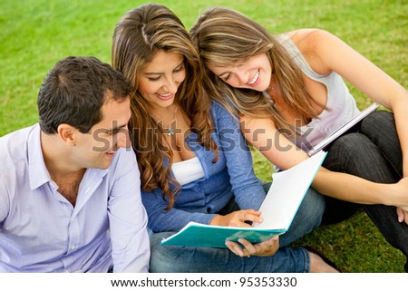 Group of friends holding notebooks and studying outdoors