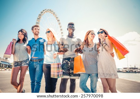 Group of friends holding shopping bags - Multiracial group of young people having fun after shopping - stock photo