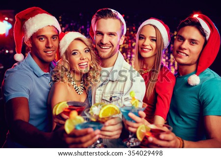 Group of friends in Santa caps holding cocktails and looking at camera