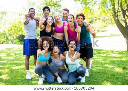 Group of friends in sportswear showing thumbs up at the park - stock photo
