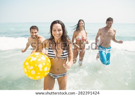 group of friends in swimsuits at the beach - stock photo