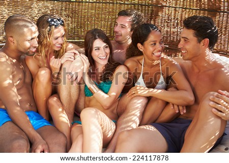 Group Of Friends In Swimwear Relaxing Outdoors Together - stock photo