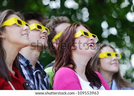 Group of friends in the park with 3d glasses looking