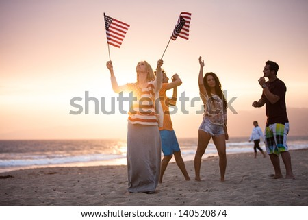 Group of Friends in their twenties dancing on the Beach at Sunset on 4th of July - stock photo