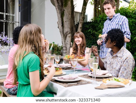 Group of friends interacting at an outdoor garden party, eating and drinking around a table - stock photo
