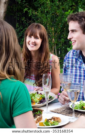 Group of friends interacting at an outdoor garden party, eating and drinking around a table