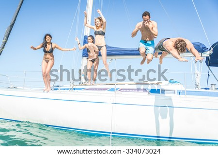 Group of friends jumping from the boat. having fun on the yacht and in the water. hot summer day and private boat party - stock photo