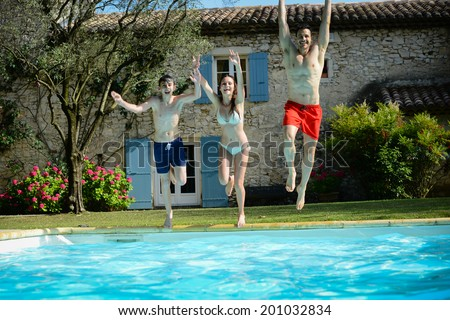 group of friends jumping in resorts swimming pool during summer holidays