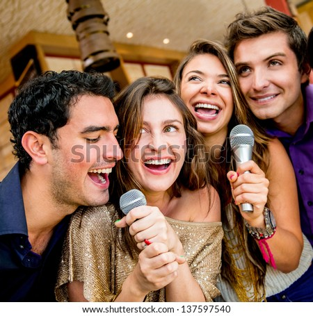 Group of friends karaoke singing at the bar - stock photo