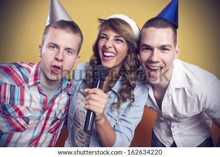 Group of friends karaoke singing at the club - stock photo