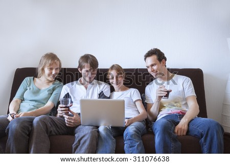 Group of friends laughing with laptop - stock photo