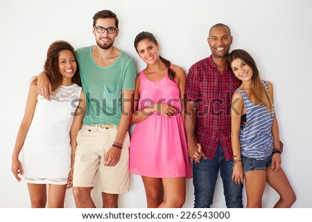 Group Of Friends Leaning Against White Wall - stock photo