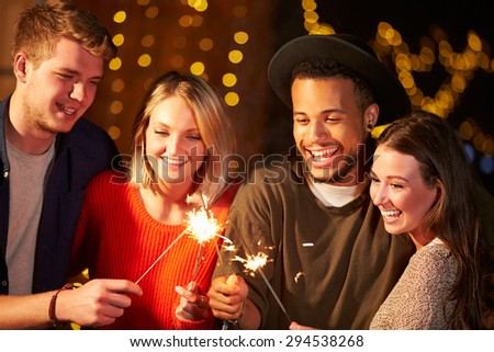 Group Of Friends Lighting Sparklers At Outdoor Party