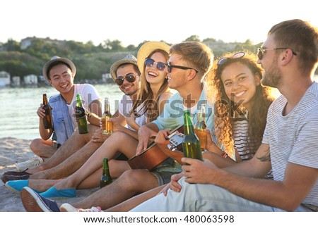Group of friends listening to guitar and drinking beer at beach