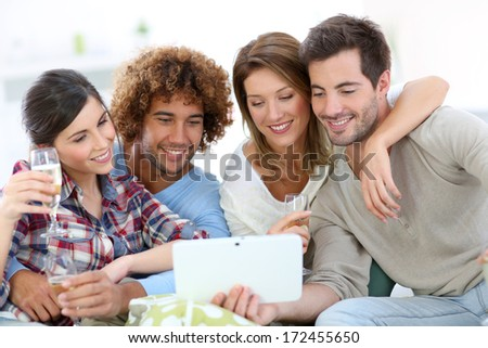 Group of friends looking at pictures on tablet - stock photo