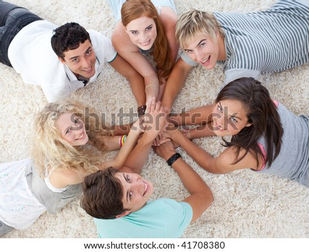 Group of friends lying on the floor with hands together - stock photo