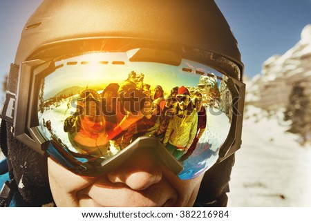 Group of friends makes selfie through goggles of their friend - stock photo