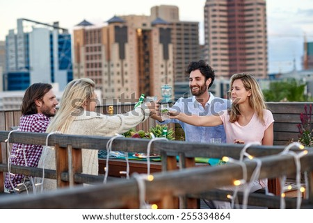 Group of friends making a toast with drinks while hanging out outdoors on the rooftop - stock photo
