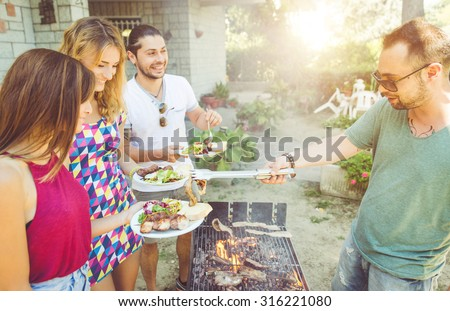 group of friends making barbecue in the garden backyard. friends sharing food and happy moments - stock photo