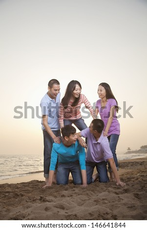 Group of Friends Making Human Pyramid on the Beach