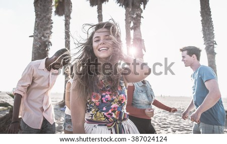 Group of friends making party on the beach and dancing together - stock photo