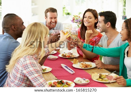 Group Of Friends Making Toast Around Table At Dinner Party - stock photo