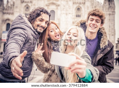 Group of friends of diverse ethnics taking a picture while grimacing - Cheerful young people photographing themselves while sightseeing a city - stock photo