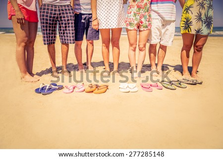 Group of friends on the beach with colored slippers on the sand - Tourists on vacation on a tropical beach during summertime - stock photo