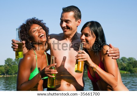 Group of friends - one man hugs two women and all have drinks in swimwear on the beach of a lake in summer - stock photo