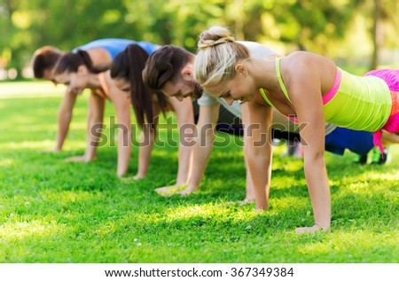 group of friends or sportsmen exercising outdoors - stock photo