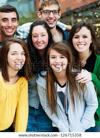 Group of friends outside together smiling - stock photo