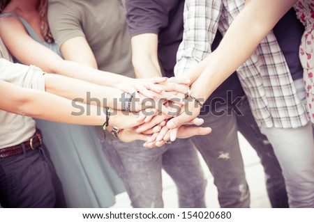 Group of friends pile up hands as unity oath,Italy - stock photo