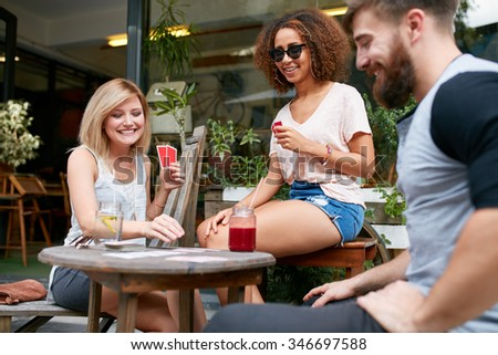 Group of friends playing a game of cards in a cafe. Woman picking up a playing card on table and smiling. - stock photo